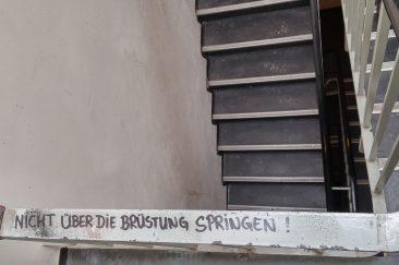 """HAU Hebbel am Ufer - Ein Treppengeländer im Backstagebereich, darauf steht in schwarzem Marker """"Nicht über die Brüstung springen""""."""