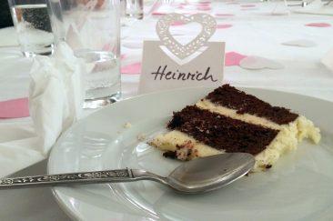 """Ein Stück Hochzeittorte auf einem Teller. Links liegt ein Löffeln. Auf dem Tisch steht ein Namensschild, darauf steht """"Heinrich""""."""