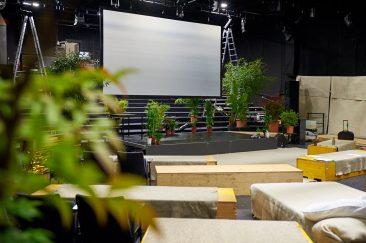 Eine große Leinwand hängt mitten im Raum. Darum herum stehen grüne Topfpflanzen. Vorn sieht man Kisten, auf denen man sitzen kann.