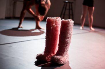 Große rosafarbene Pelzstiefel stehen auf einer dunklen Bühne. Im Hintergrund bewegen sich zwei Tänzer. Alles wirft scharfe Schatten.